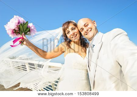 Young newlyweds with bouquet taking selfie against blue sky - Wedding couple cheering together after ceremony - Lovely life concept with groom and bride celebrating love forever on a warm sunny day