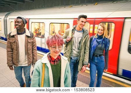 Multiracial group of hipster friends having fun in tube subway station - Urban friendship concept with young people walking together in city underground area - Vivid color with focus on pink hair girl