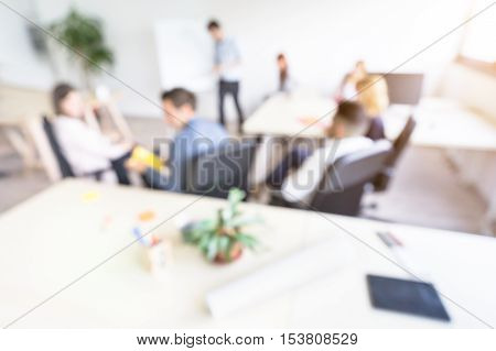 Blurred defocused background of businesspeople meeting with concentrated start up entrepreneur coworkers - Business concept with young people team in modern minimal office - Bright desaturated filter