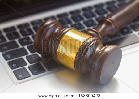 Wooden law gawel on laptop keyboard close up, judgement concept