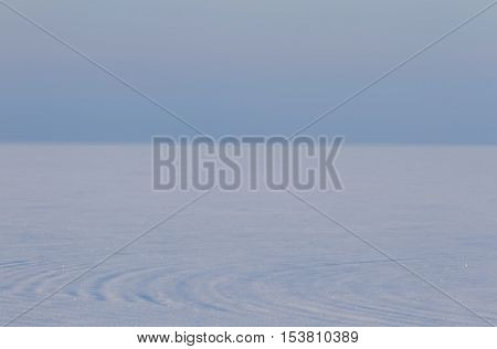 Blue winter snowscape background with swirling snow texture foreground