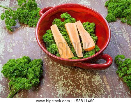 Portion of fresh cutted herbs and carrots in a clay bowl