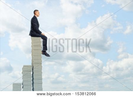 Businessman sitting on the top of a pile of stocks looking at a cloudy sky. Reach its climax. Achieve results. Complacent. Being on the top. Financial well-being.