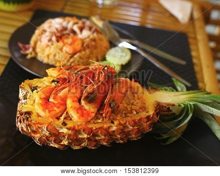 Freshly prepared pineapple fried rice with seafood - prawn squid octopus served inside of a pineapple carved like a bowl.
