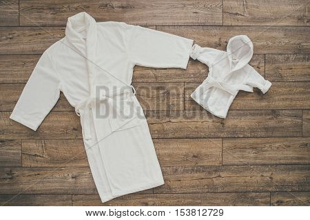Two white bathrobes for mom and baby. Holding hands. wooden background
