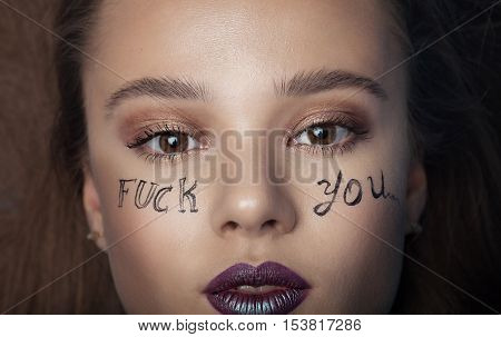 Woman with writing fuck you on her face. Creative make up