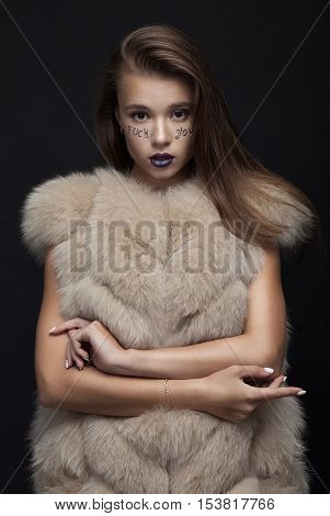 Beauty Fashion Model Girl in Blue Mink Fur Coat. Beautiful Luxury Winter Woman with creative make writing fuck you on face