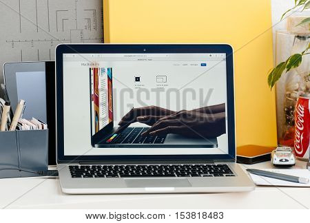 PARIS FRANCE - OCT 28 2016: Apple Computers website on new MacBook Pro Retina with OLED touch bar in a geek creative room showcasing new professional laptop - detail of hands wotking on laptop using the touch bar and the keyboard