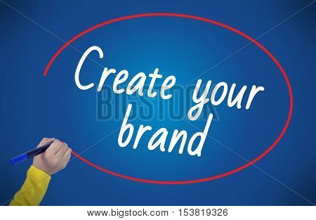 Woman hand writing create your brand with marker on blue background professionally