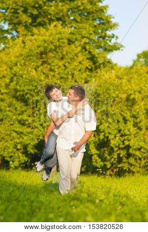Family Values. Happy Caucasian Family of Father and Son Piggybacking Outdoors. Against Nature Green Forest. Vertical Image