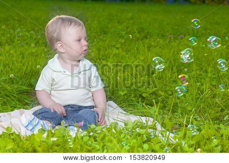 Natural Portrait of Little Cute Caucasian Toddler Child Sitting on Grass Outdoors. Horizontal Image Orientation