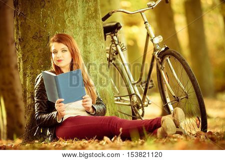 Relax intellectual cycling fitness nature outdoor concept. Lady reading under tree. Smiling red haired woman sitting holding book next to bike.