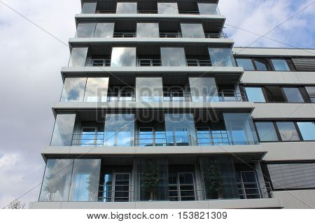 Modern glass building with the built in trees. Architectural innovative construction. Office building with balconies and trees.
