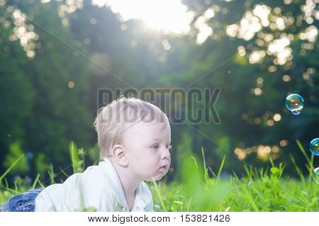 Portrait of Little Cute Caucasian Boy Playing With Soap Bubbles Outdoors. Horizontal Image Composition