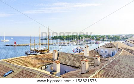 Krk island Croatia at sunset. The port with boats docked at marina the red lighthouse on the mole ceramic tiles on the roof houses.