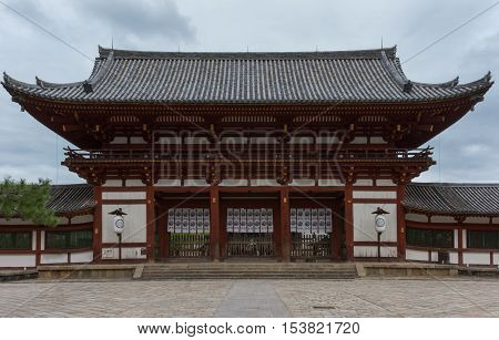 Nara Japan - September 21 2016: Large wooden entrance gate to the Todai-ji Buddhist temple grounds. Leads to the inner courtyard in front of temple building. Gray roof white walls dark wood.