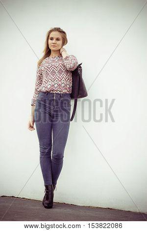 Urban style. Stylish fashionable beauty woman with black bag handbag. Blondie girl model posing outside. Fashion of female idea.