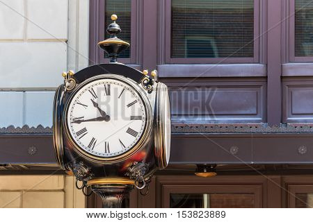 Old Vintage Clock on top of a lamp post on the city street. Large clock face with analog hands.
