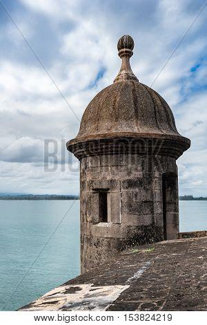 Castillo San Felipe del Morro tower turret with cloudy sky and aqua water in San Juan Puerto Rico