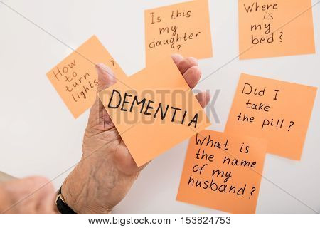 Close-up Of Person's Hand Holding Dementia Sticky Note At Home