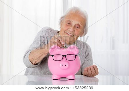 Happy Senior Woman Inserting Coin In Piggybank On Table