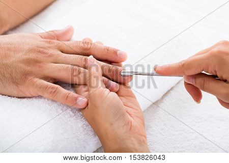 Close-up Of A Manicurist Removing Cuticle From Person's Nail
