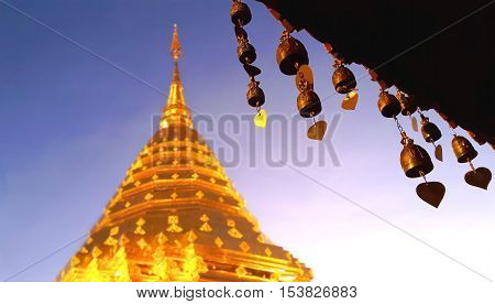 Buddhist brass bell at the roof of thai temple with soft blurred golden stupa Wat Phra That Doi Suthep Chiang mai Thailand