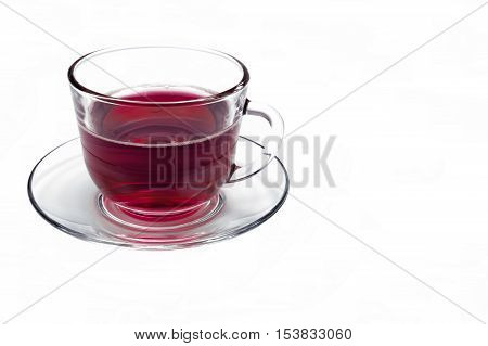 transparent glass cup with Hibiscus tea on a saucer isolated on a white background