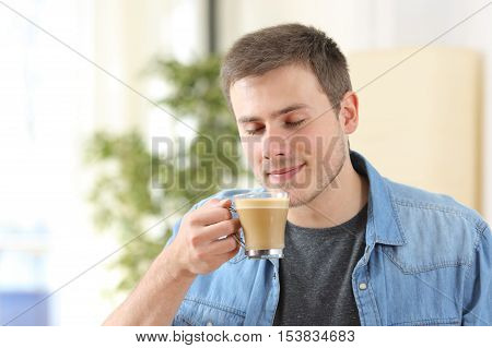 Man tasting coffee with milk and smelling its aroma at home