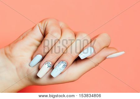 glamour female hand and fingers with fashionable trendy nail polish white color on fingernails has soft skin of young human on orange background closeup