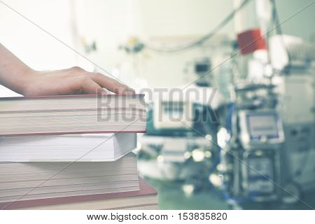 Hand on the book against the background of medical equipment.