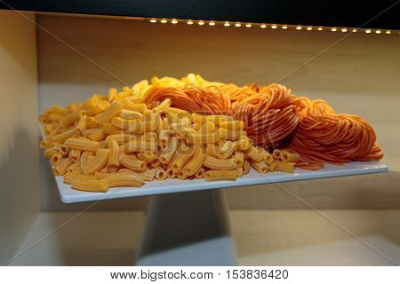 Uncooked Penne Italian Pasta And Red Spaghetti Shown On White Dish