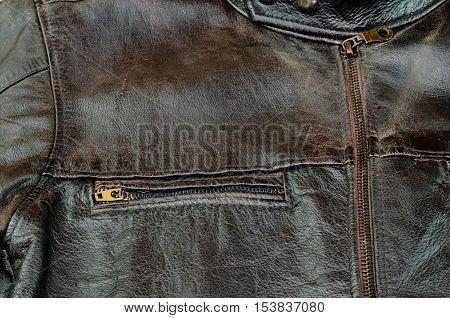 Old black leather jacket closeup black backgrounds