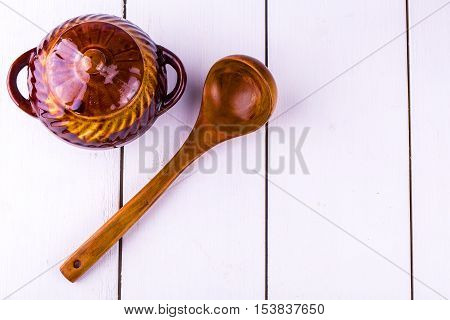 old crock pot cooking and wooden sppon on white wooden background. View from above