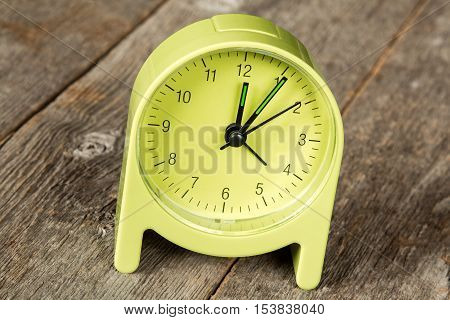 Green alarm clock showing five minute past twelve hour