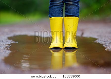 Child Wearing Rain Boots Standing In A Puddle