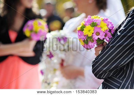 Row of bridesmaids with bouquets on summer day