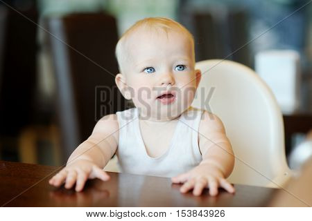 Six month old baby girl sitting by the table