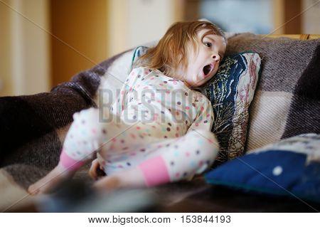 Little sleepy girl in pajamas yawning on summer day