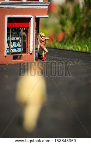 Small figurine of prostitute on street corner and men silhouette.