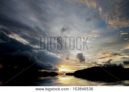Beautiful sunset above the river and dark sky