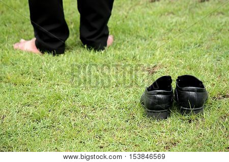old black leather shoes and legs on green grass