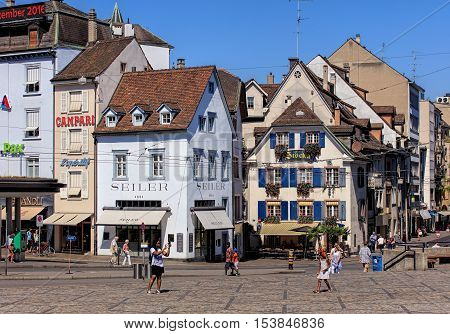 Basel, Switzerland - 27 August, 2016: people and buildings on Barfuesserplatz square. Basel is a city on the Rhine river in northwestern Switzerland, situated where the Swiss, German and French borders meet.