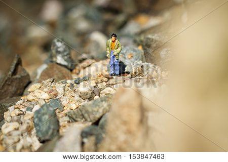 Small hiker figure walking in rocky moutain.