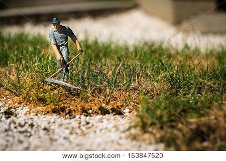 Gardener small figurine with a scythe cutting grass.