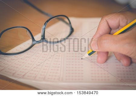 optical form of an examination with pencil and glasses filling a standardized test form