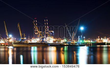 NOVOROSSIYSK, RUSSIA-30 APRIL, 2016: Cargo ships in the container terminal. Illuminated cargo port in Novorossiysk at night with container terminals cargo ships and cranes.