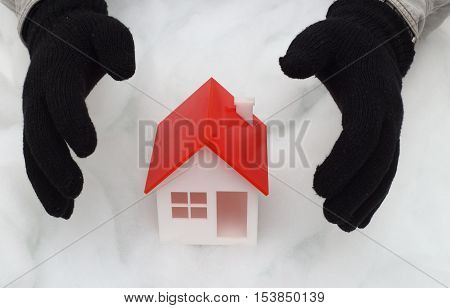 Model of house guarded by hands in winter gloves
