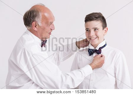 Elegant Grandfather Helping His Grandon With Collar