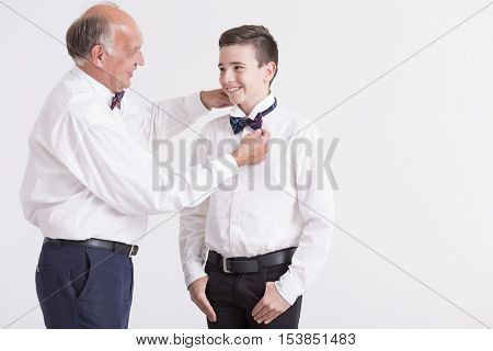 Man Correcting The Dicky Bow Of His Grandson